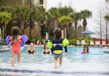 Young children entering swimming pool at Orange Lake Resort near Orlando, Florida