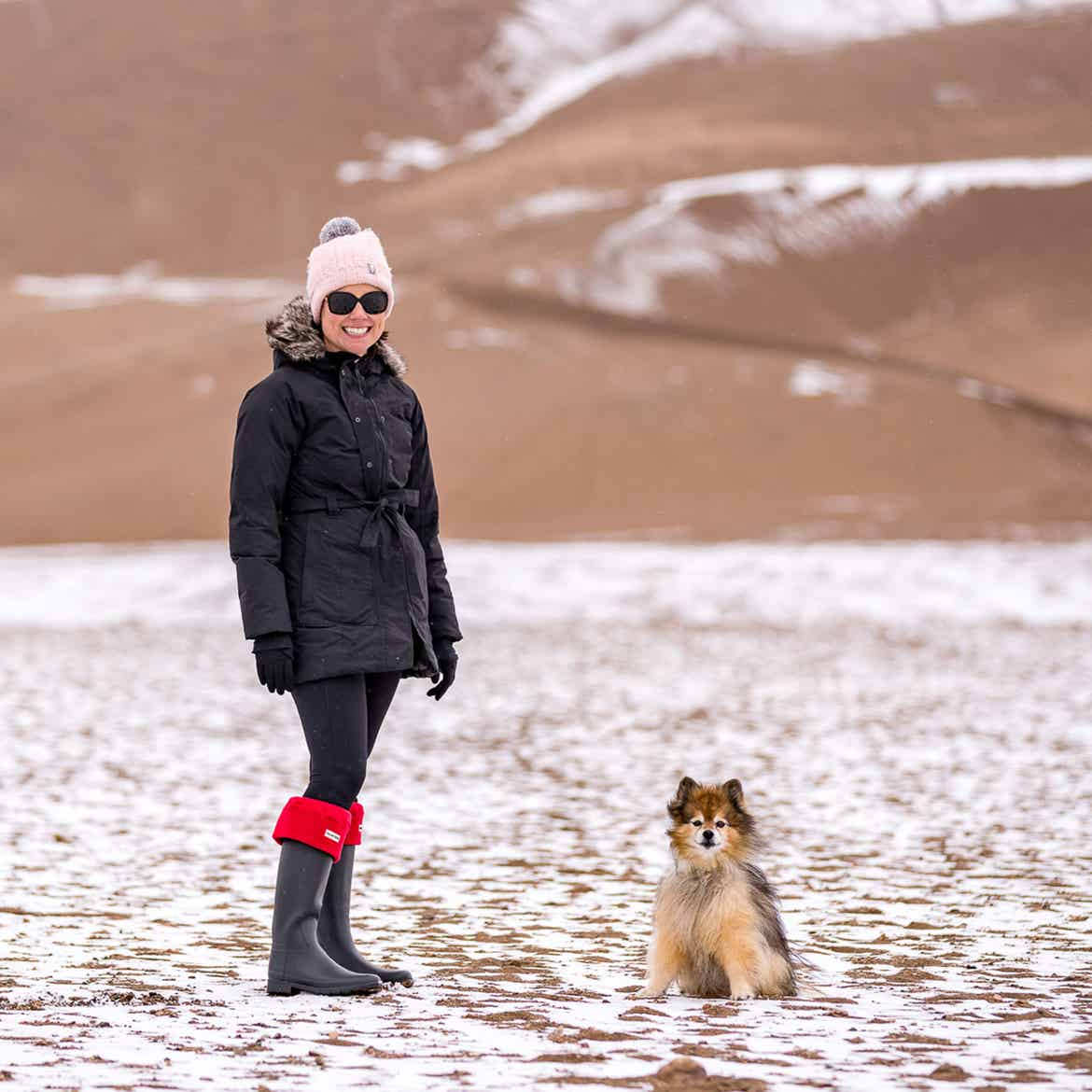 Author, Lauren Layne, stands in winter apparel with Bailey the Pomeranian at the Great Sand Dunes National Park and Preserve.
