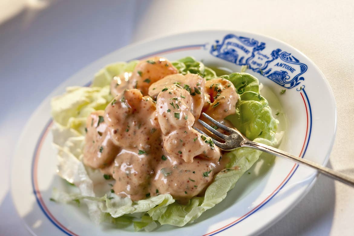 A white plate with blue toile imprint that reads 'Antoines' containing shrimp in Antoine's rémoulade.