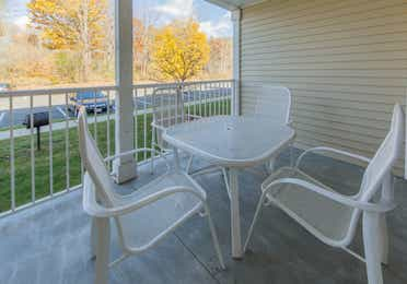 Patio overlooking trees and a parking lot in a two bedroom presidential villa at Oak n' Spruce Resort in South Lee, Massachusetts