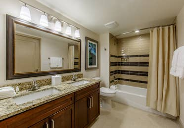 Full bathroom with a shower/tub combination, his and hers sinks, and toilet in a three-bedroom villa at Scottsdale Resort