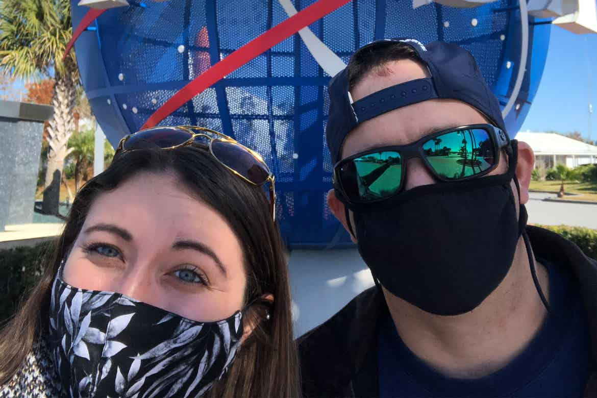 Featured contributor and Checking In editor, Tori Ferrante (left), and her husband, Brooks (right) wear masks in front of the NASA globe outside of Kennedy Space Center in Cape Canaveral, Florida.