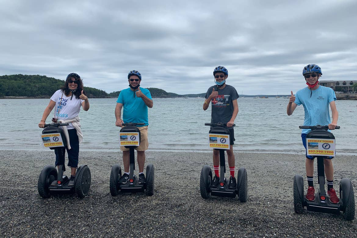 Jennifer (left) and her family stand on Segway's wearing helmets and masks for their safety along the edge of the waterfront.