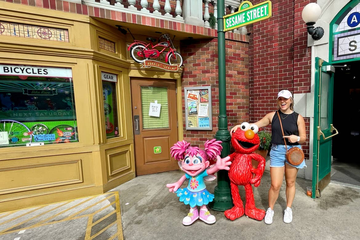 A Caucasian woman with a pink baseball cap, black tank, denim shorts and white shoes stands next to statues of Elmo and Abby Cadabby at Sesame Street Land™ in SeaWorld Orlando.