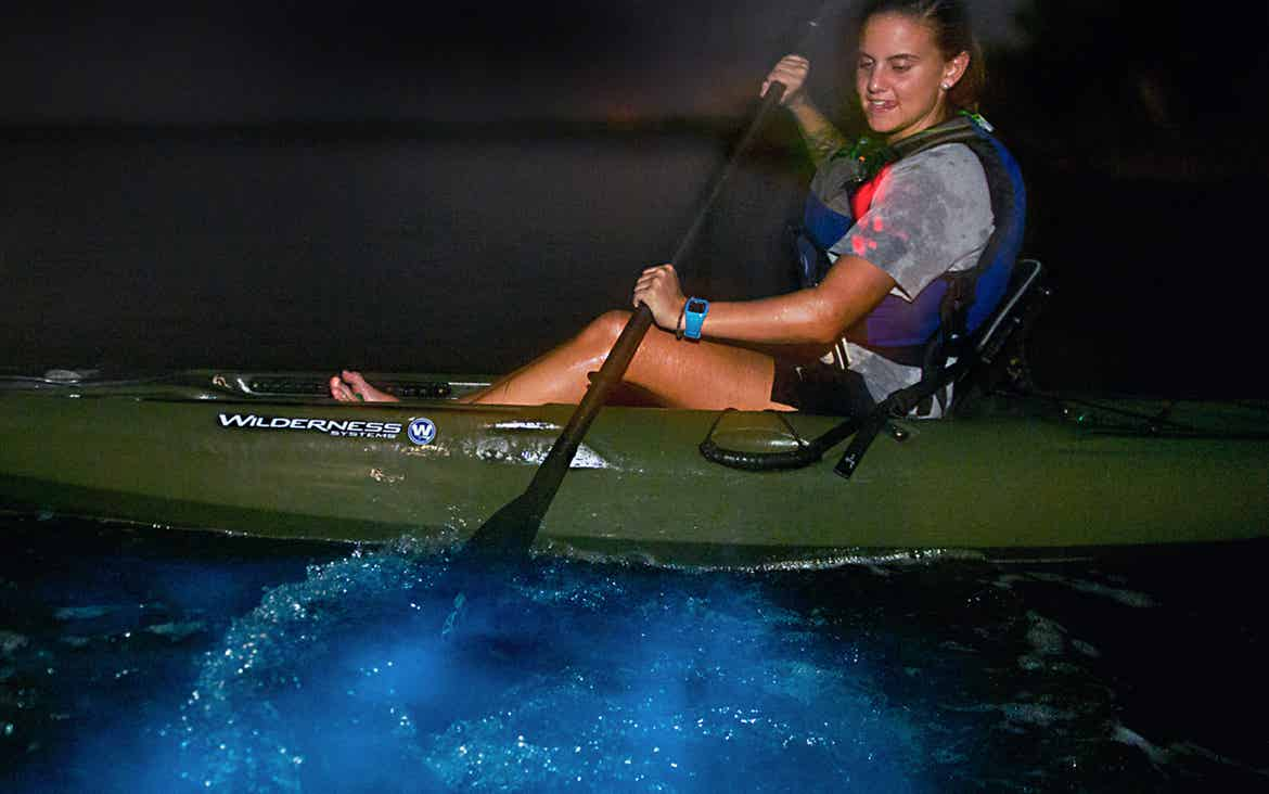 Girl padding a kayak in glowing waters in Florida's Indian River