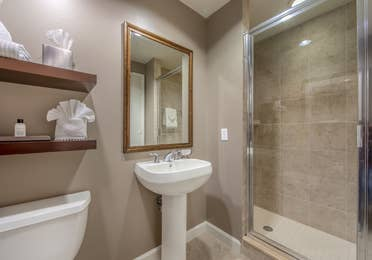 Bathroom with walk-in shower, sink with mirror above, and toilet in a three-bedroom villa at Sunset Cove Resort in Marco Island, Florida