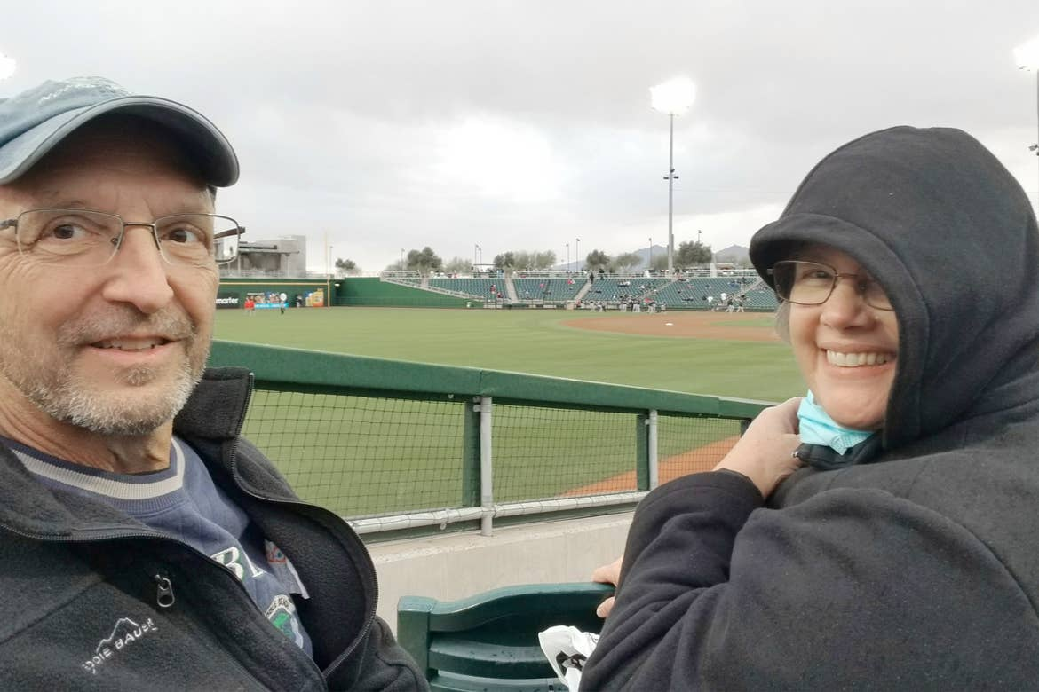 A caucasian man (left) and woman (right) wear dark jackets, glasses and sit near a baseball field under s cloudy sky.