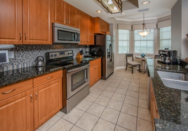 Full kitchen with stainless steel oven, microwave, fridge, and sink in a three-bedroom villa at Sunset Cove Resort