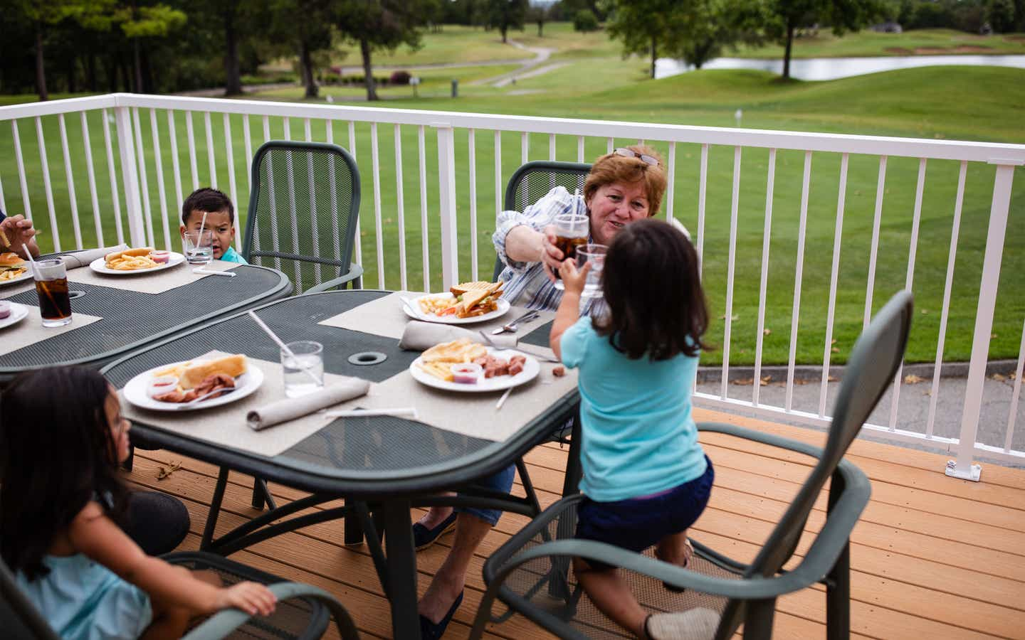 Family eating outdoors at The Grille on the Greens at Holiday Hills Resort in Branson, Missouri.