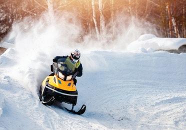 A man is racing a snowmobile through the snow.