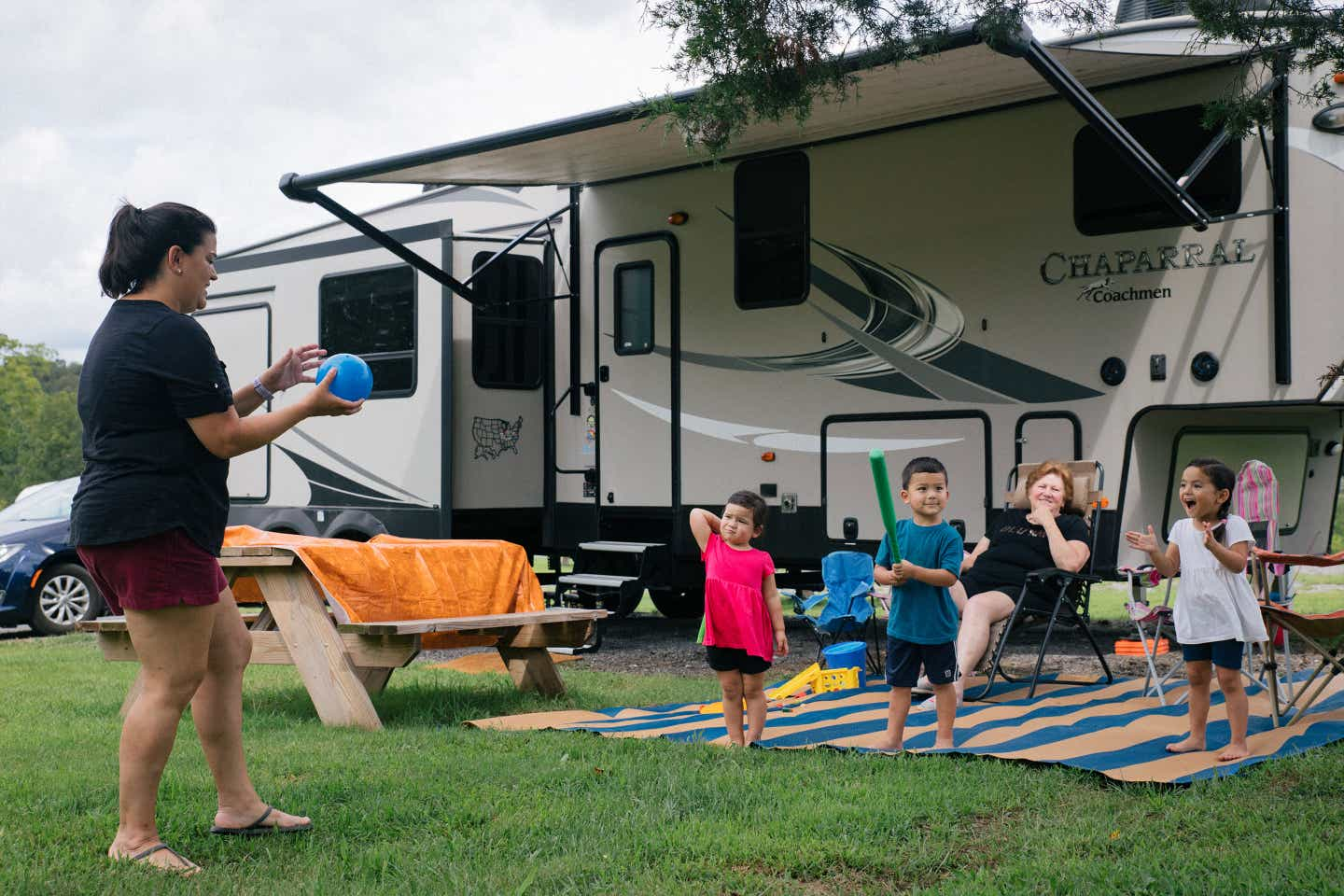 Angelica (left) plays with her three children outside their RV with her mother looking onward behind the children.