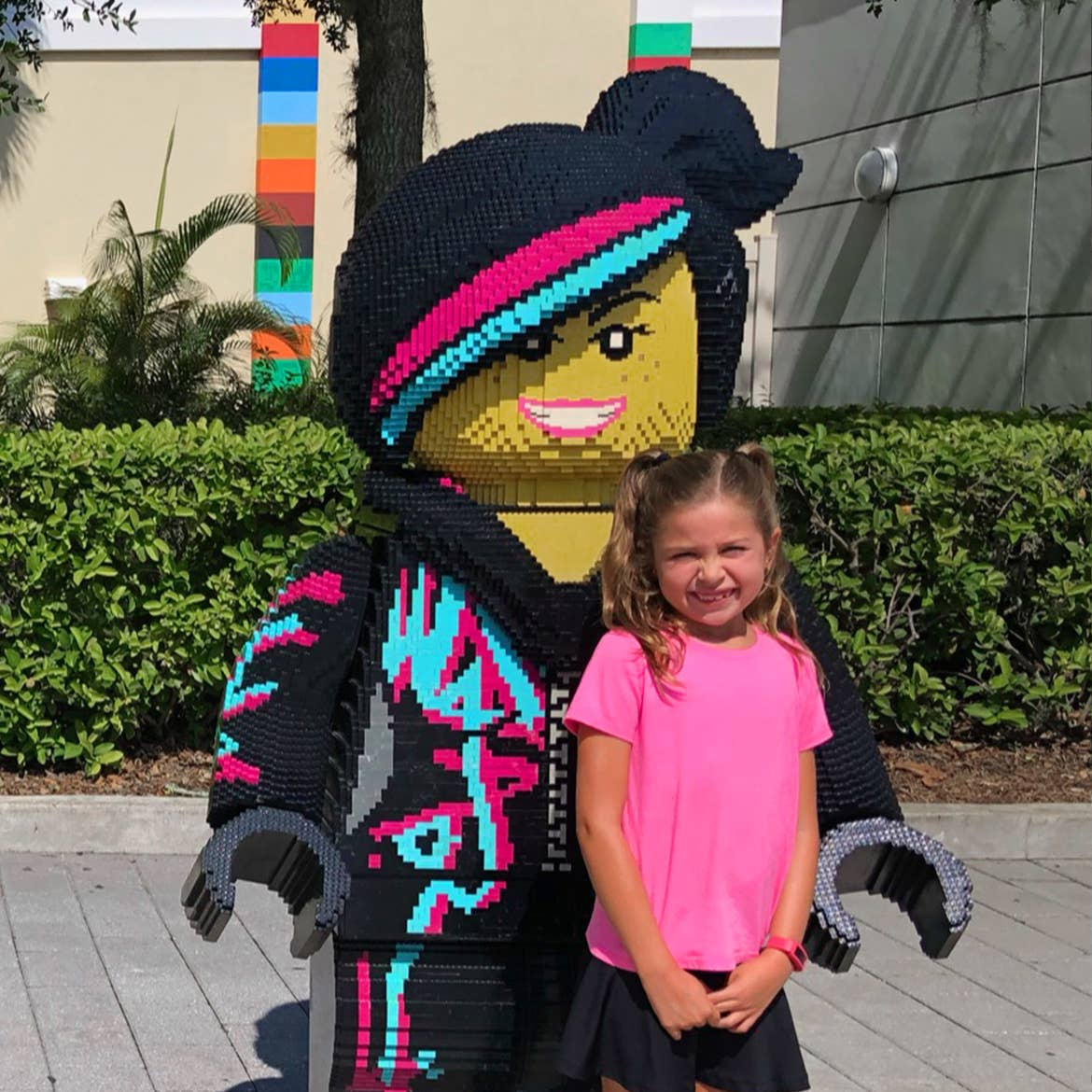 A young girl in a pink t-shirt (right) stands next to an oversized LEGO figure.