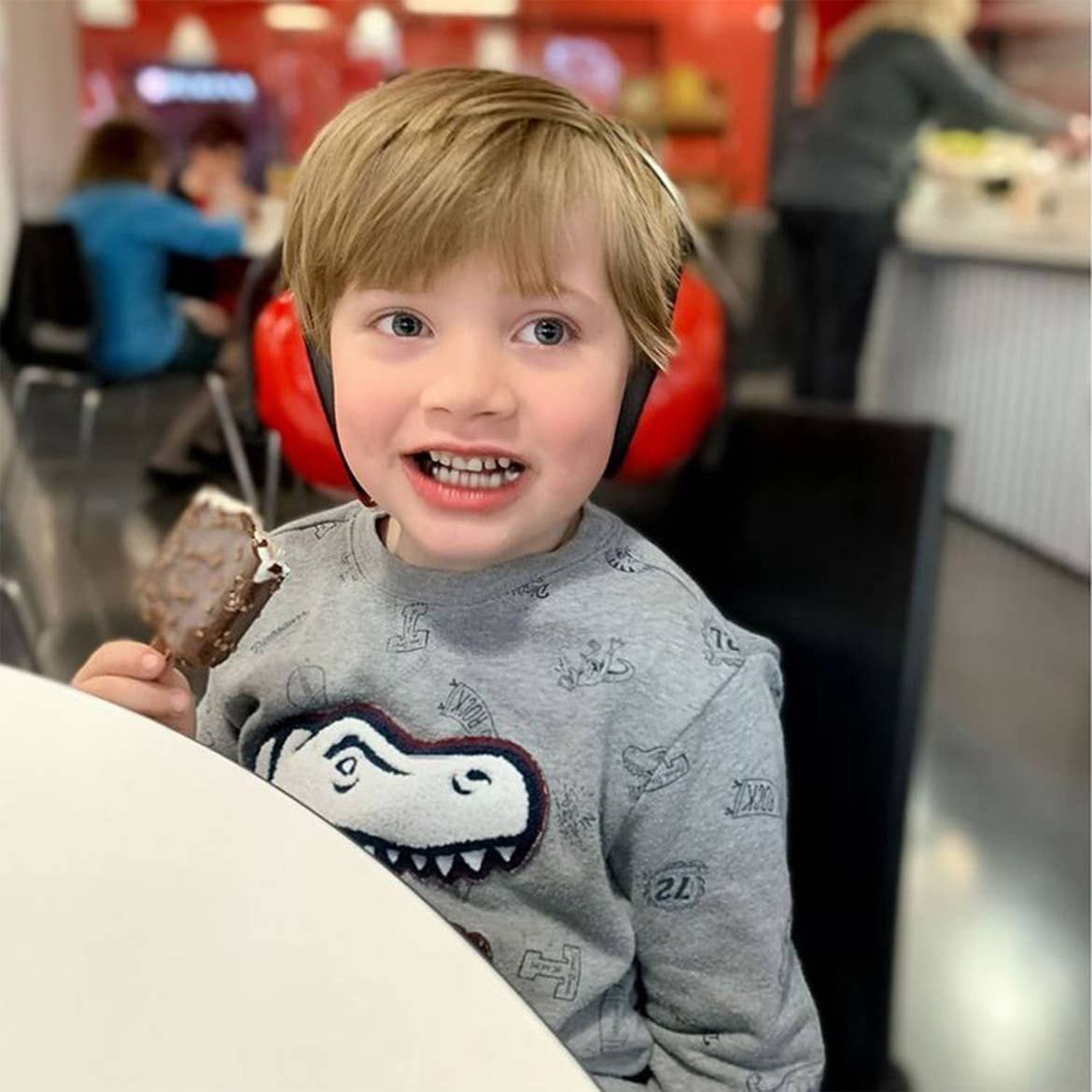 Featured Contributor, Alicia Trautwein's son eats an ice cream bar while wearing red headphones at a dining table indoors.