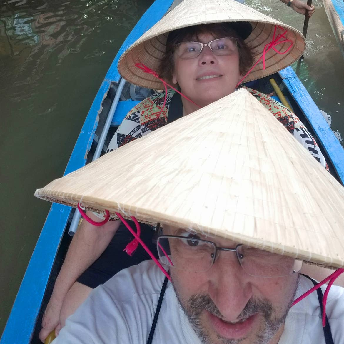 A caucasian man (front) and a caucasian woman (back) wear Vietnamese straw hats on a blue passenger kayak on the Mekong Delta in Vietnam.