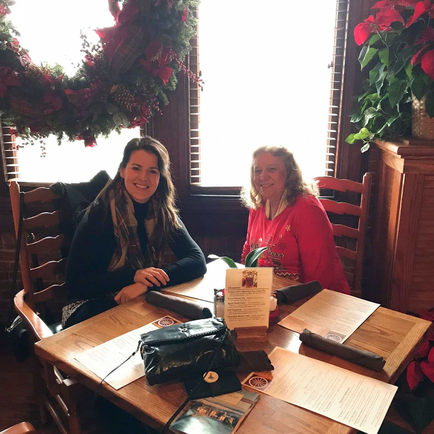 Author, Jenn C. Harmon (left), and her mother-in-law (right) seated near a table in front of a window while dining at the Stable Cafe.