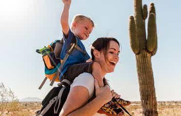 Jessica and her son laughing together while he sits on her shoulders as they hike in the Arizona desert.