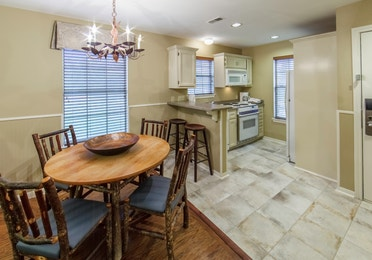 Dining table and kitchen in a three-bedroom ambassador villa at the Hill Country Resort in Canyon Lake, Texas.