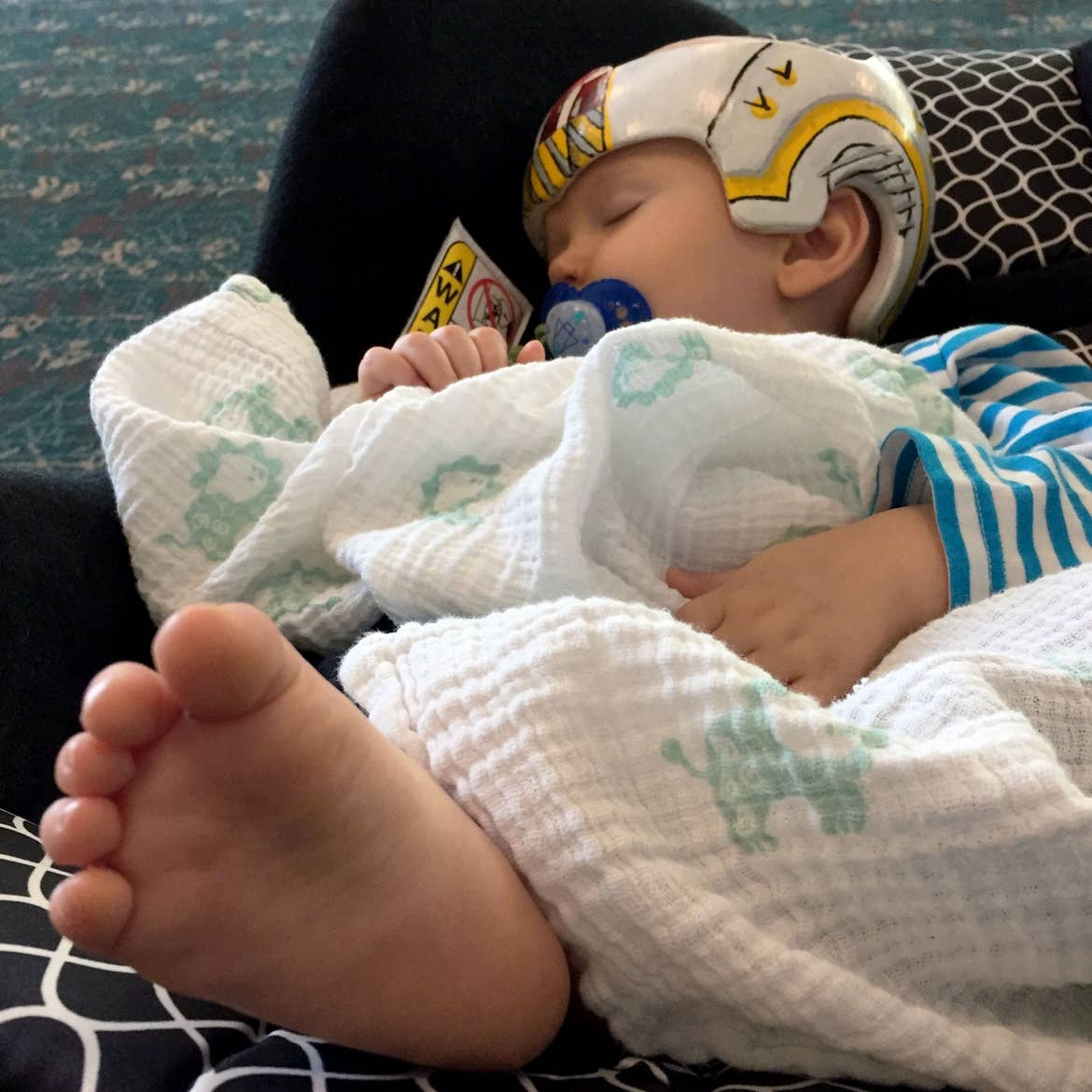 Sarah's son, Logan, sits bundled in his car seat as they await to board the airplane.