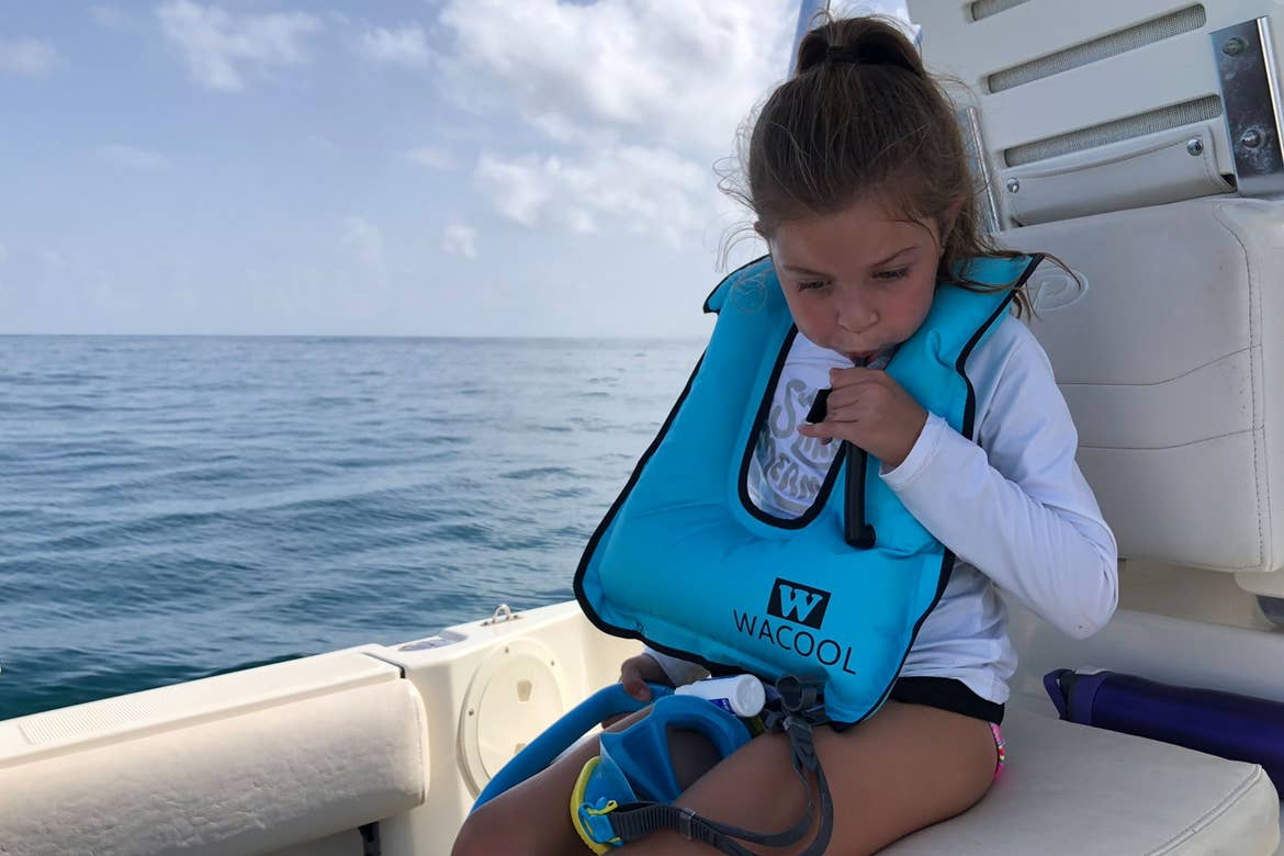 Featured Contributor, Chris Johnston's daughter, Kyler inflates her Wacool snorkel vest while sitting on a boat in the ocean.