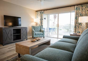 Living room with couch, chair, flat screen TV and balcony in a villa at Cape Canaveral Beach Resort.