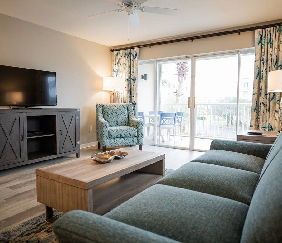 Living room with couch, chair, flat screen TV and balcony in a two-bedroom villa at Cape Canaveral Beach Resort.