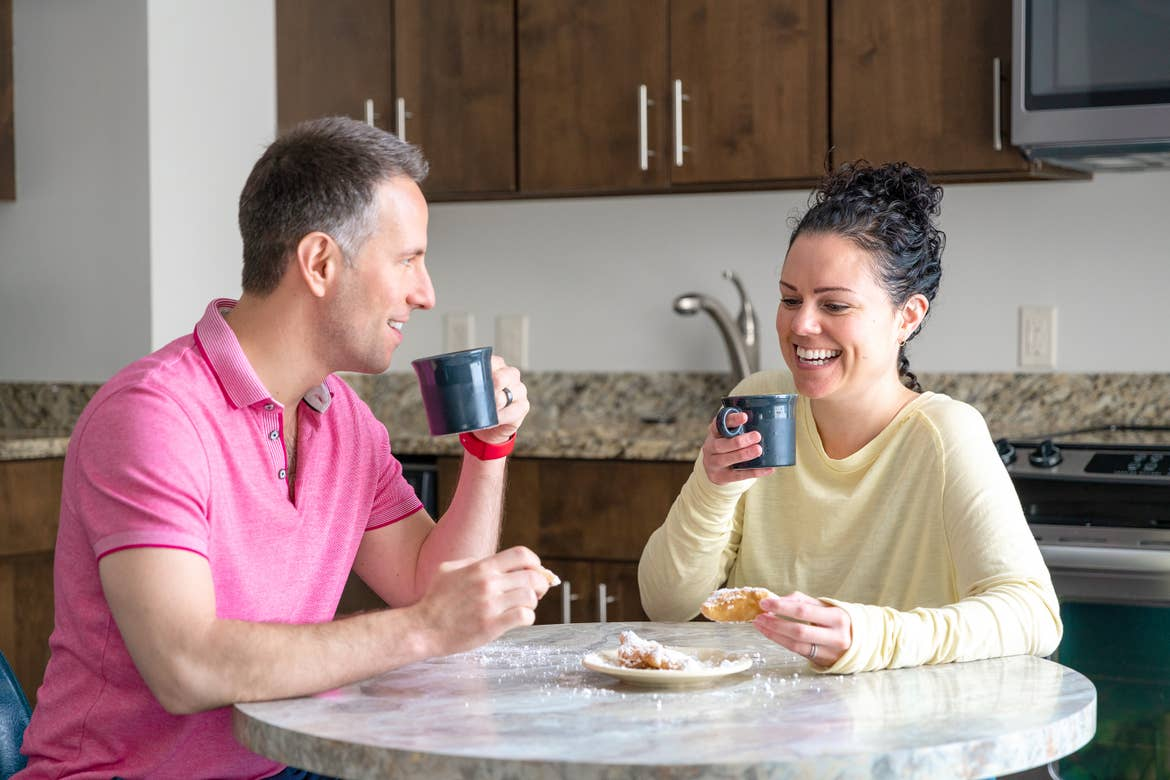 A man (left) wears a pink polo shirt while holding a blue mug in his left hand at a round dining table next to a woman (right) wearing a yellow long-sleeve shirt holding a blue mug in her right hand.