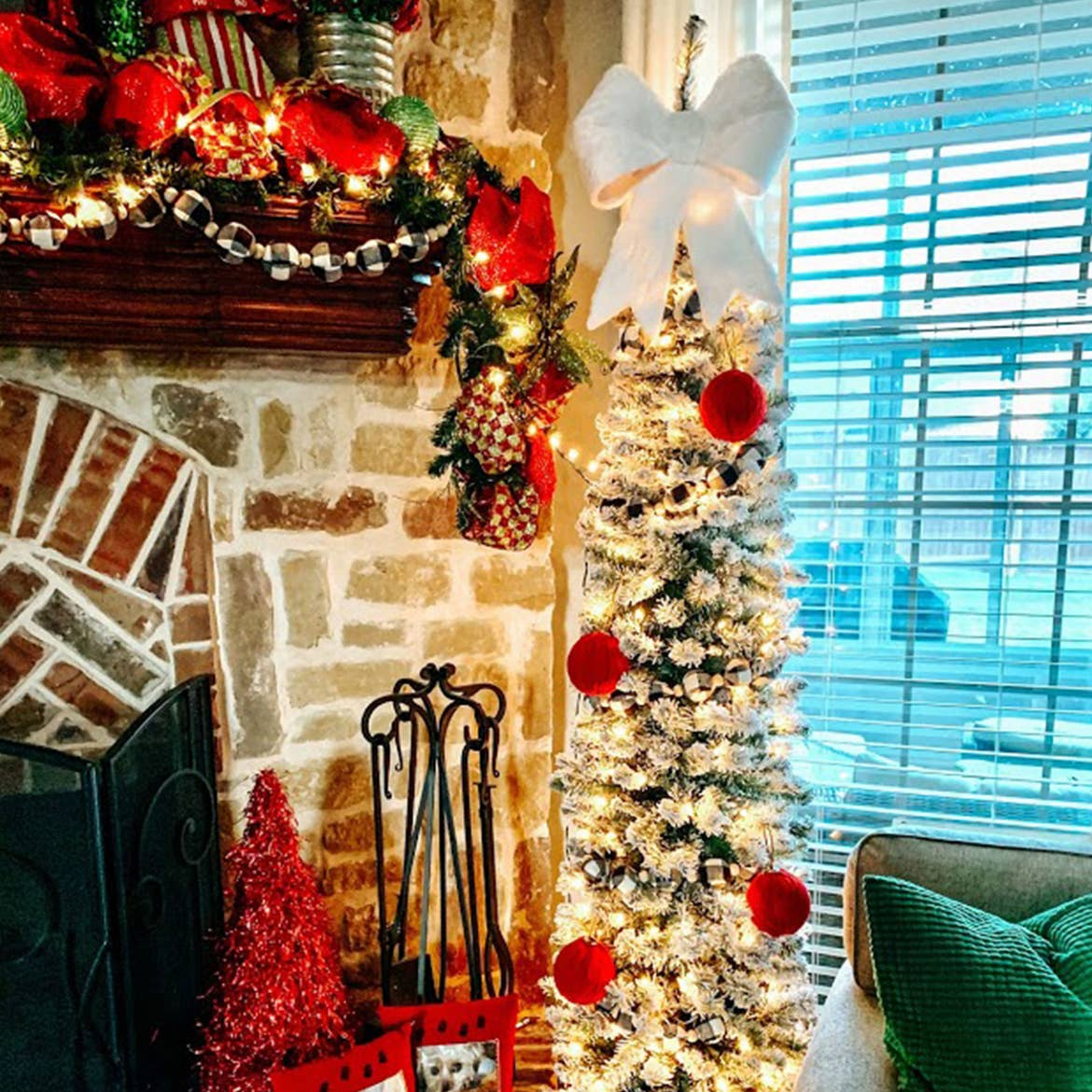 A small 'pencil tree' decked out in holiday decor next to a mantle.