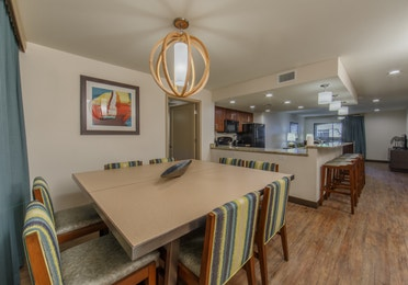 Dining table with eight chairs and kitchen in background in a three-bedroom villa at Scottsdale Resort