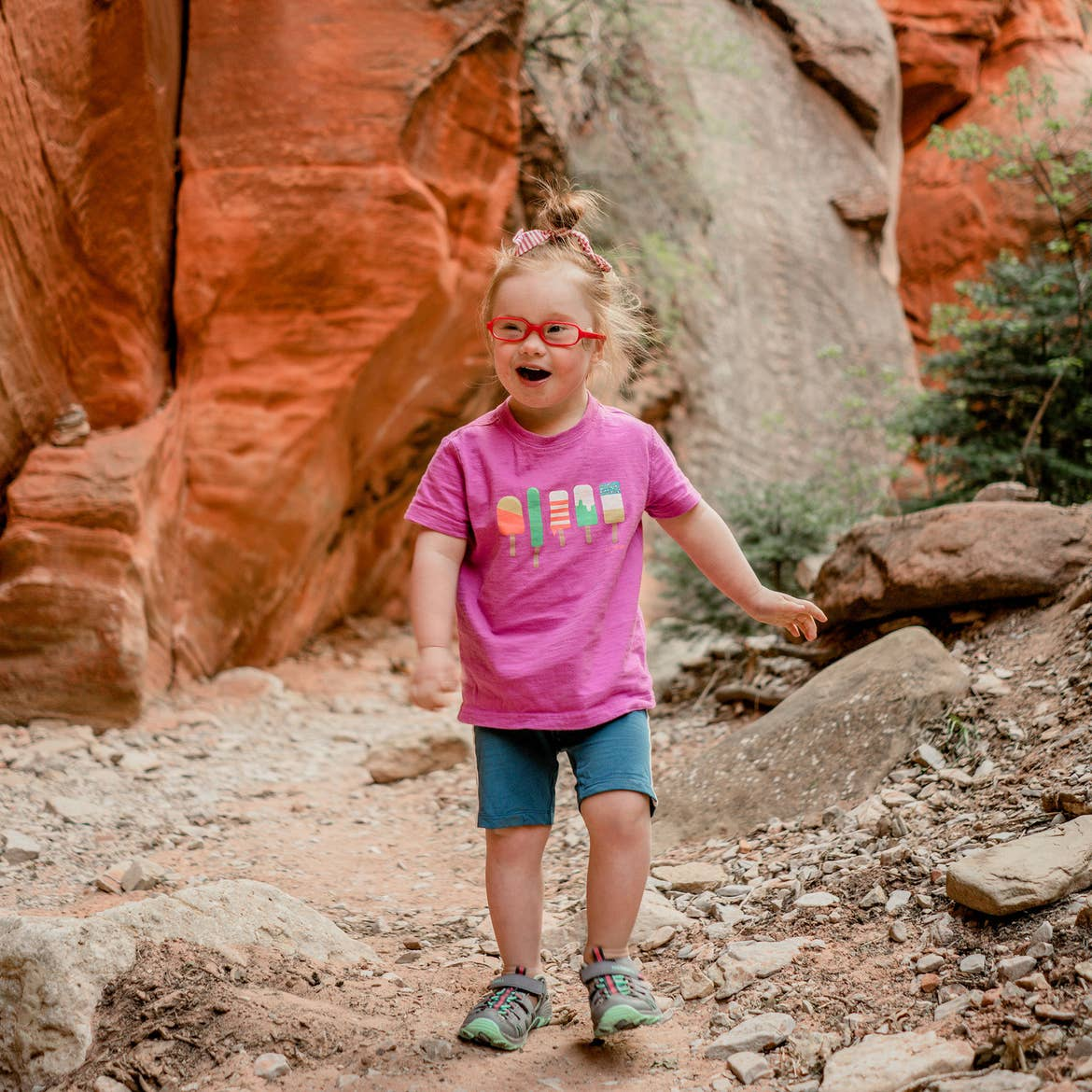 Featured Contributor, Melody Forsyth's daughter, Ruby walks in front of a rock formation in a pink t-shirt and shorts.