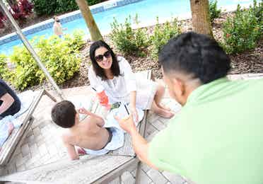 Family lounging on sun chairs by lazy river at Orange Lake Resort near Orlando, Florida