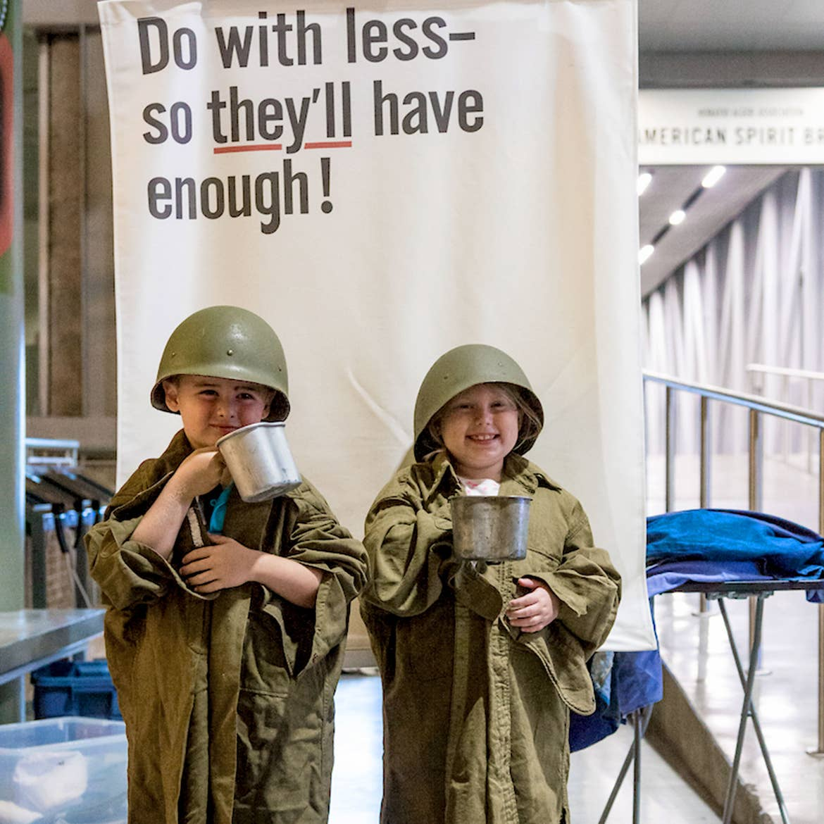 Two children recreate WWII propaganda dressed in 'Army Greens' and a helmet while holding silver mugs in front of a sign that reads, 'Do with less- So they have enough!'