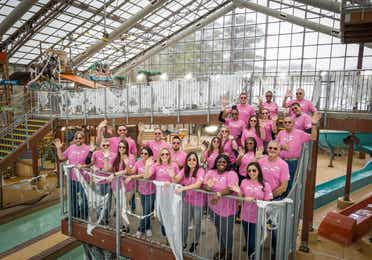 A group of volunteers standing in an indoor water park facility and waving at the camera.