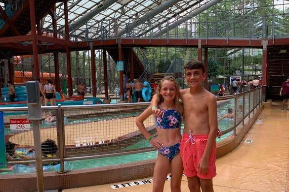 A caucasian girl (left) and boy (right) stand in swimsuits near an indoor waterpark.