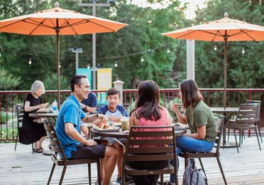 Family eating on outdoor patio at Grill at Villages Resort in Flint, Texas.