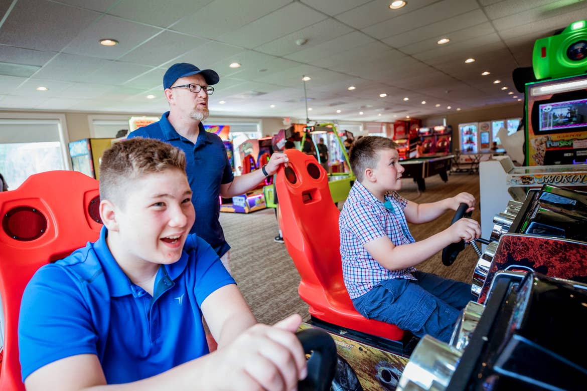 A caucasian man (middle) wearing a navy baseball cap and polo stands behind two tween, caucasian boys (left and right) seated in an arcade racing game seat behind a steering wheel.