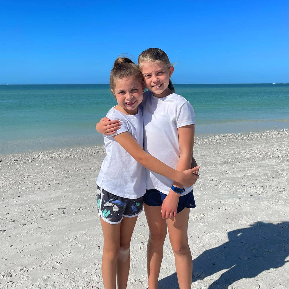 Two caucasian girls wearing white t-shirts and running shorts stand on a beach.