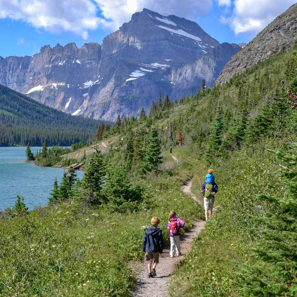 Featured Contributor, Jessica Averett's family walk a trail near Glacier Lake at Glacier National Park.