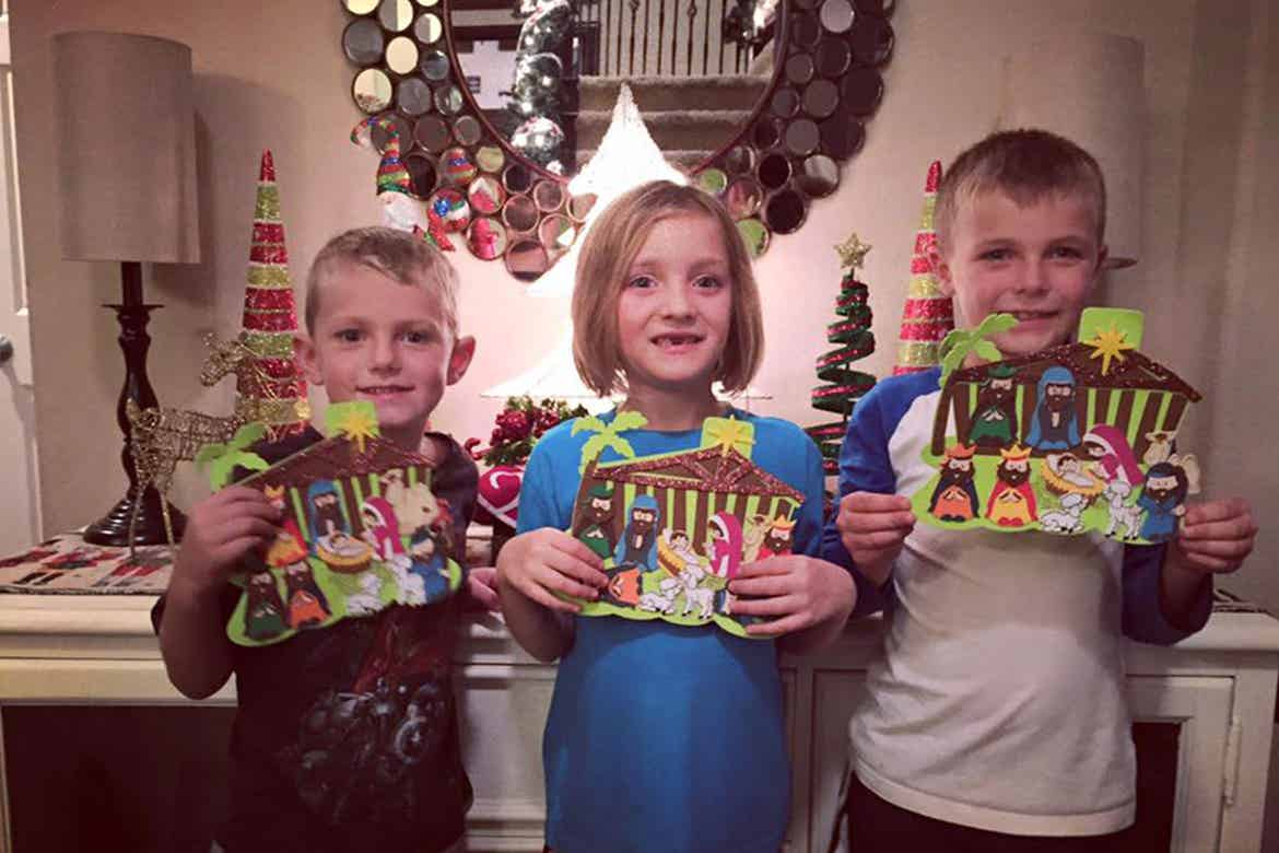 Three children hold up their crafted paper Nativity scenes in front of some holiday decorations.