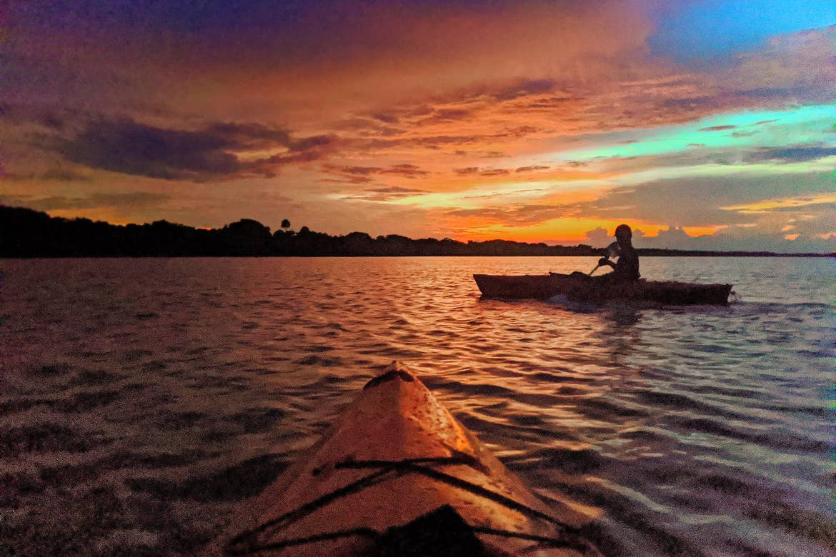 A man on a red kayak paddles under a sunset in the Mosquito Lagoon at Merritt Island National Wildlife Refuge where bioluminescence glows.