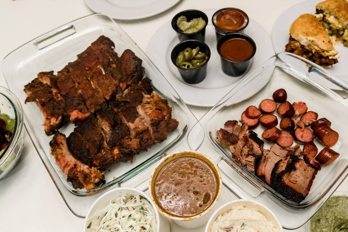 Various barbecued meats placed on clear glass plated surrounded by white plates containing toppings, sauces and sides on a white table.