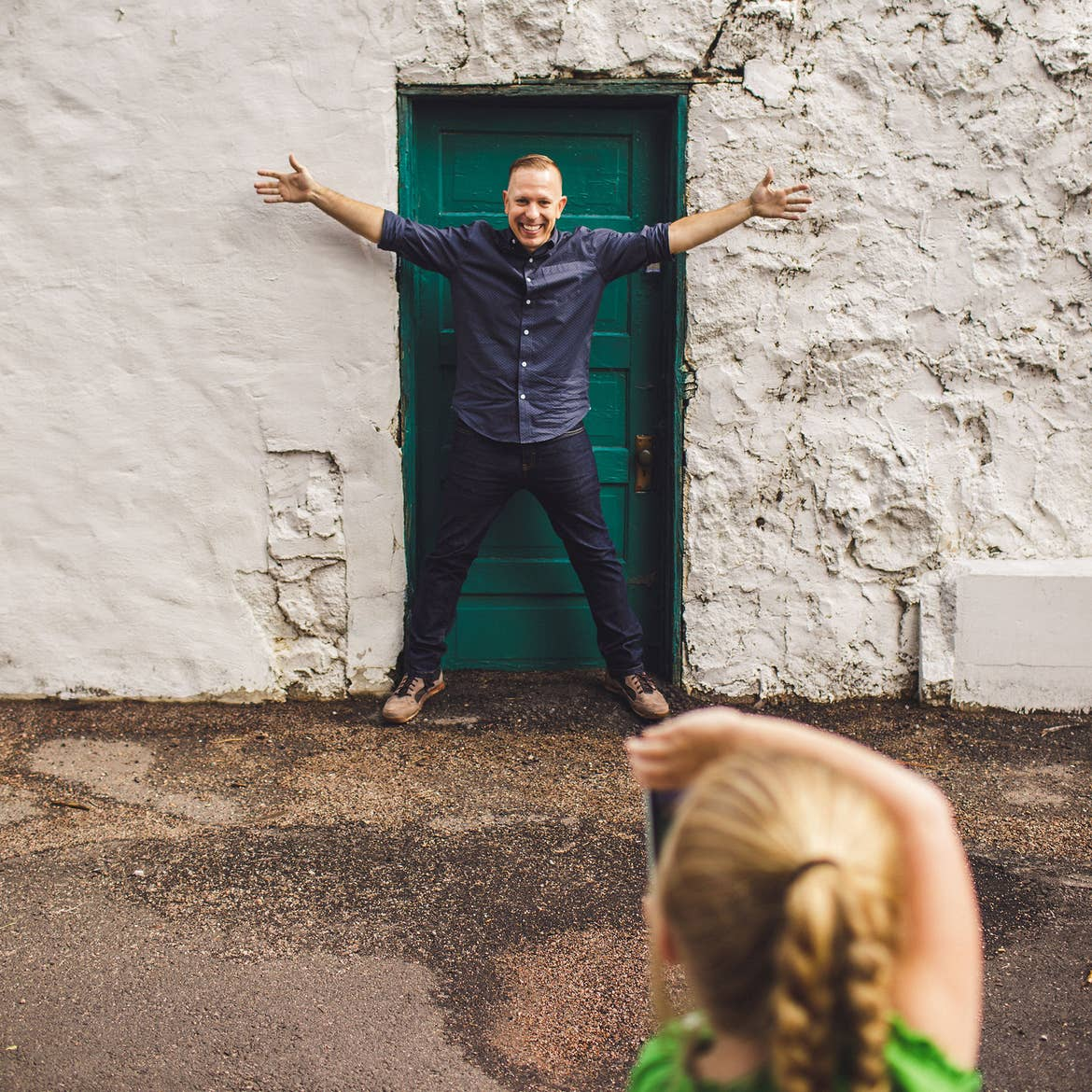 A father stands in front of a green door posing excitedly while his daughter takes his photograph.