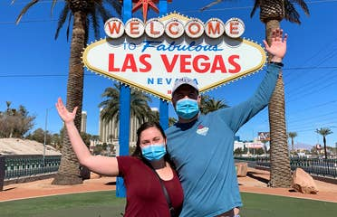 Featured Contributor, Ashley Fraboni (left) and her fiancé, Nicholas (right), pose in front of the 'Welcome to Las Vegas' marquee while wearing face masks.
