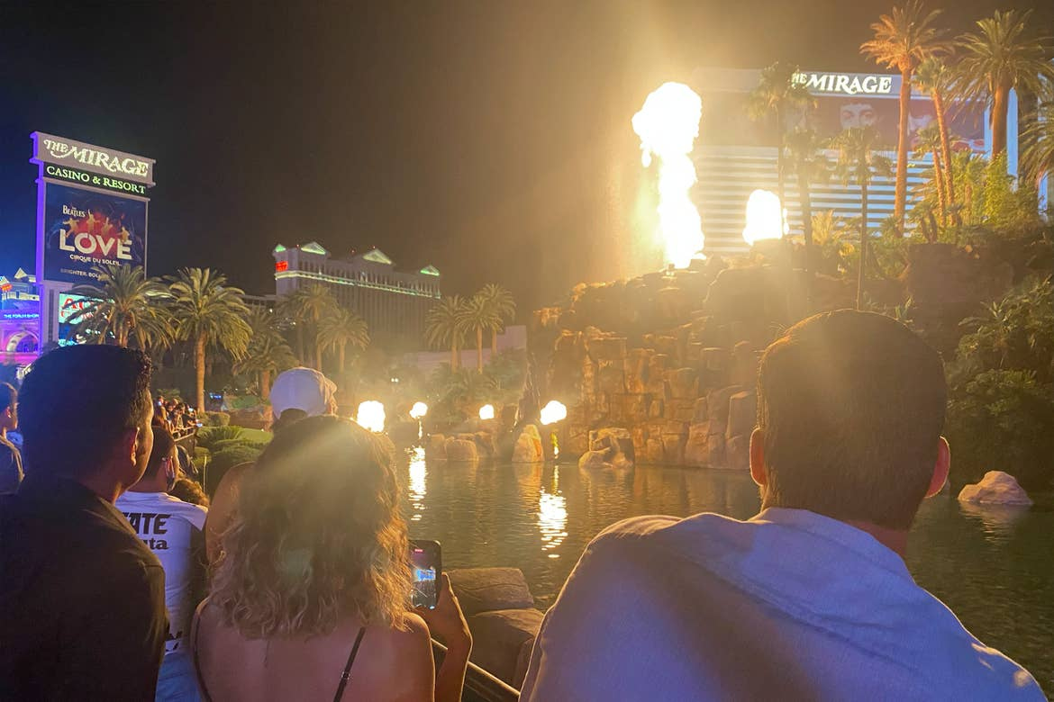 A group of tourists watch a pylon of fire erupt from the Volcano simulation outside of the Mirage hotel under the night sky.
