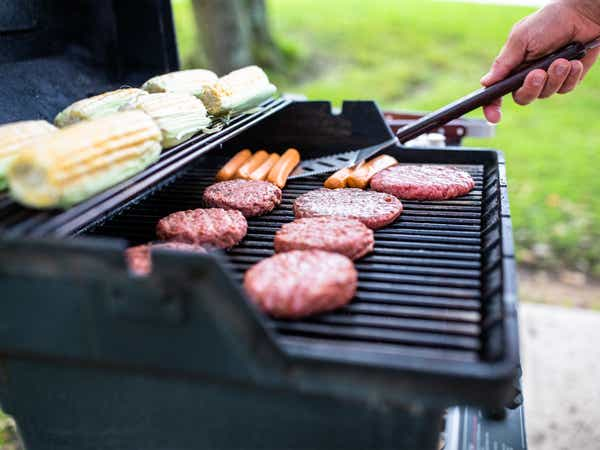 Person grilling corn, hotdogs and hamburgers at Villages Resort in Flint, Texas.