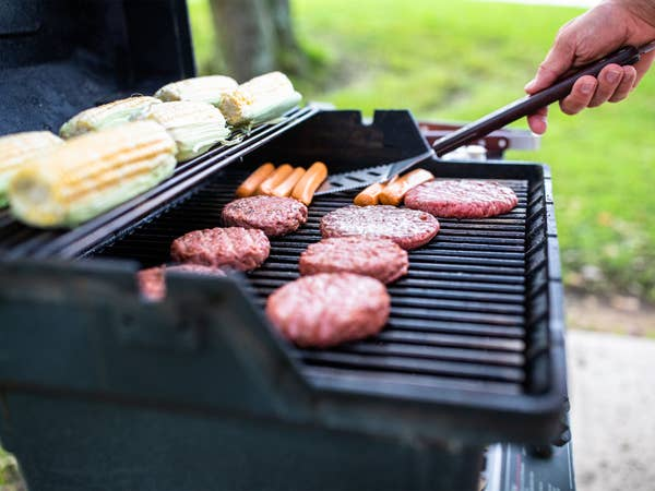 Person grilling corn, hotdogs and hamburgers at Villages Resort in Flint, Texas.