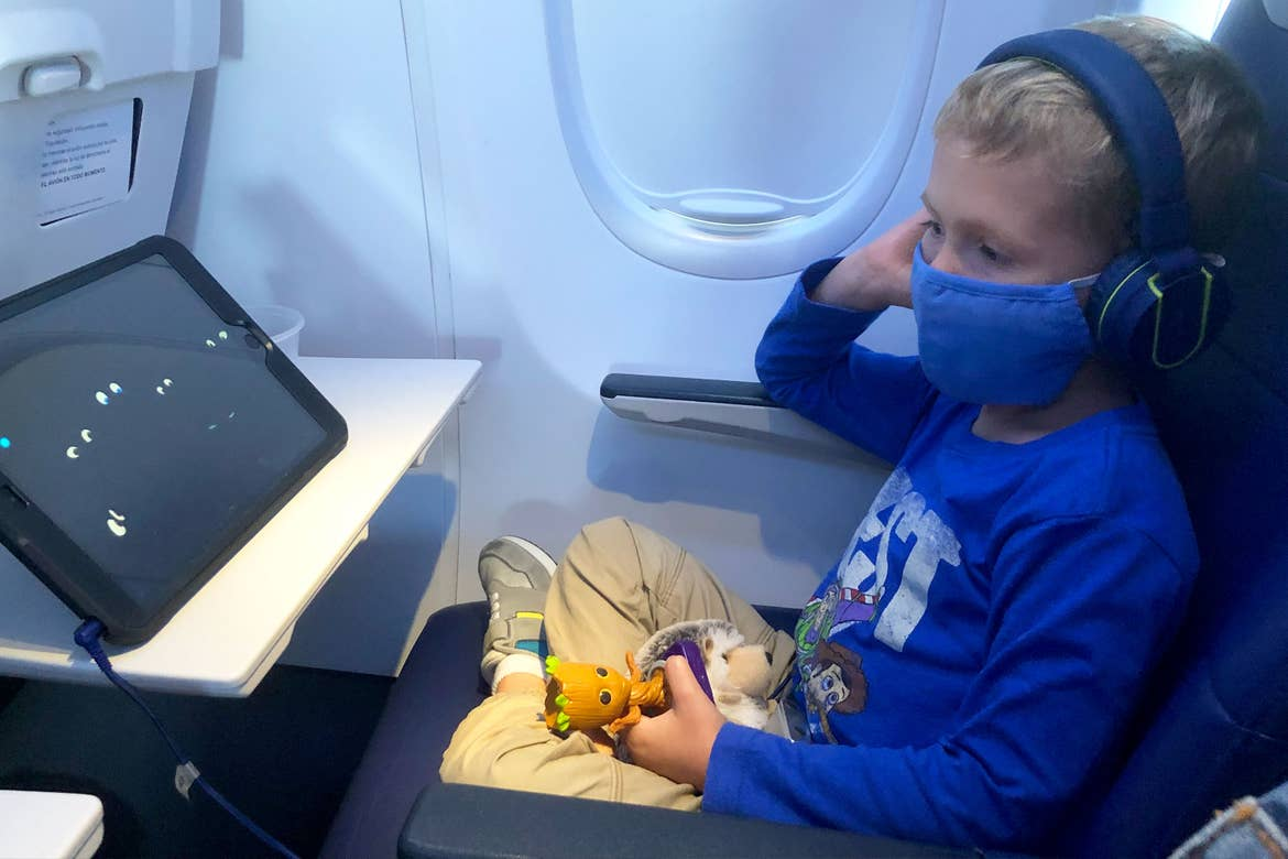 Sarah's son, Logan, sits on the airplane with his mask and entertainment on the tray.