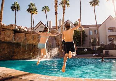 Two kids jumping into outdoor pool at Desert Club Resort in Las Vegas, Nevada.