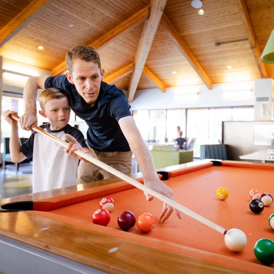 Adult and young child playing billiards at Scottsdale Resort in Scottsdale, Arizona.