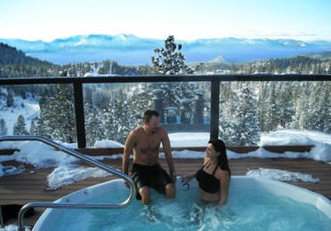 Couple sitting in a hot tub in the winter overlooking Lake Tahoe at Tahoe Ridge Resort