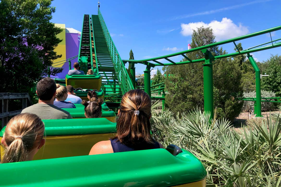 A young girl (left) and woman (right) sit several rows behind guests on a green outdoor rollercoaster.